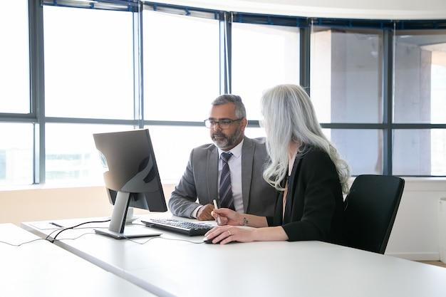 Dos colegas enfocados viendo y discutiendo contenido en el monitor de la computadora, sosteniendo el lápiz y el mouse y hablando mientras están sentados en la sala de reuniones con ventana panorámica. concepto de comunicación empresarial