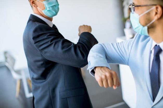 Dos colegas evitan un apretón de manos cuando se reúnen en la oficina y saludan con golpes de codos