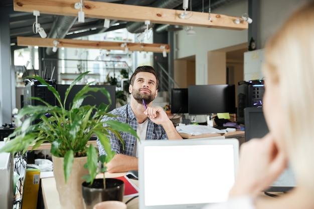 Dos colegas felices en el coworking de la oficina mientras usan computadoras portátiles