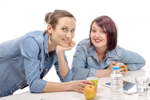 Dos colegas femeninas están haciendo un descanso para tomar café