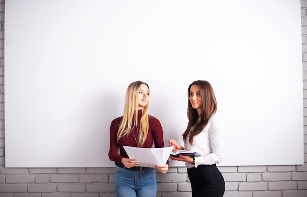 Dos colegas femeninas en la oficina trabajando juntos.
