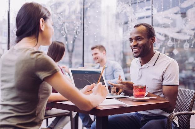 Dos colegas inteligentes ambiciosos posando en el café mientras prueban el nuevo software y el hombre sonriendo