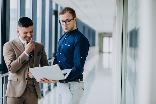 Dos colegas masculinos en la oficina, de pie con laptop