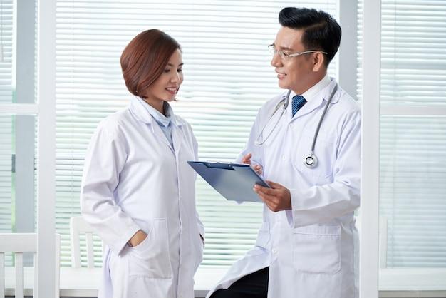 Dos colegas médicos discutiendo la agenda en la sesión informativa