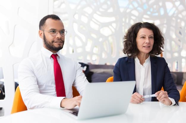 Dos colegas de negocios entusiasmados que escuchan a socios