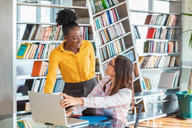Dos colegas de negocios mirando la computadora portátil y discutiendo su plan de inicio en la oficina moderna