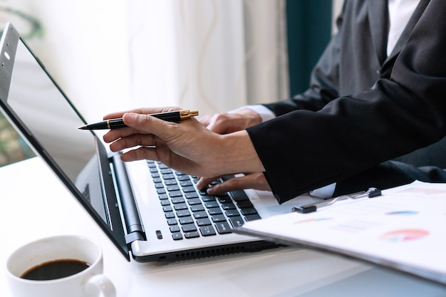 Dos colegas que discuten datos con la computadora portátil del ordenador en la tabla del escritorio en oficina. cierre de análisis de equipo de negocios y concepto de estrategia.
