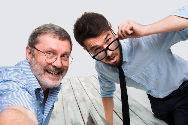 Dos colegas que les toman la foto sentados en la oficina