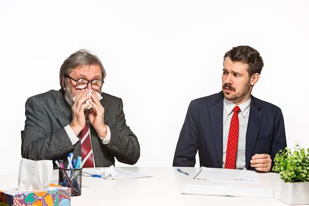 Los dos colegas que trabajan juntos en la oficina en blanco.