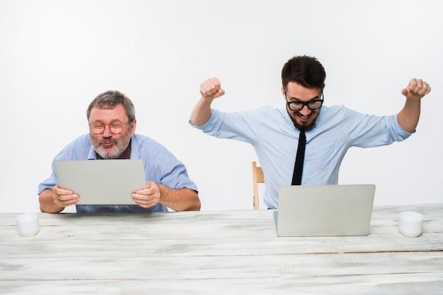 Los dos colegas que trabajan juntos en la oficina en la pared blanca