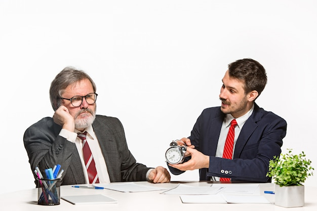 Los dos colegas que trabajan juntos en la oficina sobre fondo blanco.