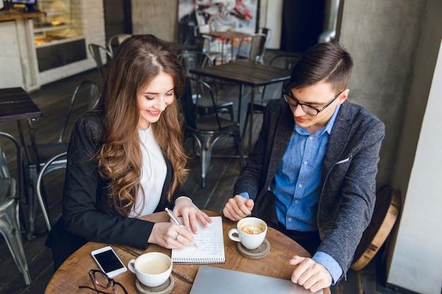 Dos colegas sentados discutir un proyecto en un café