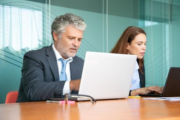 Dos colegas sentados juntos y usando computadoras en la oficina. empleados de diferentes edades escribiendo en teclados de portátiles.