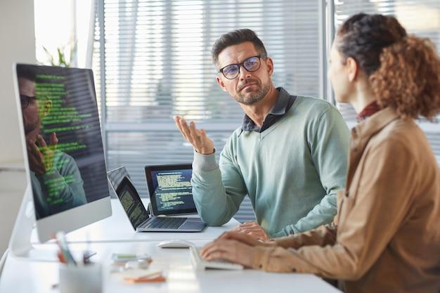 Dos colegas sentados a la mesa frente a las computadoras y discutiendo el nuevo software en la oficina de ti