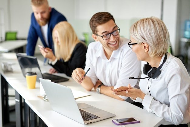 Dos colegas se sienta a hablar en el trabajo, sonriendo. diviértete, feliz concepto de cooperación
