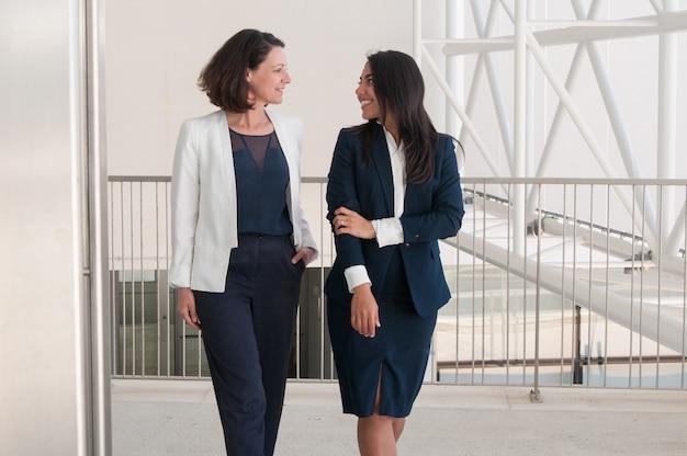 Dos colegas sonrientes hablando y caminando en la sala de oficina