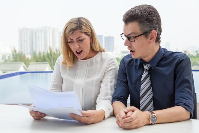 Dos colegas sorprendidos mirando a través del informe de negocios al aire libre.