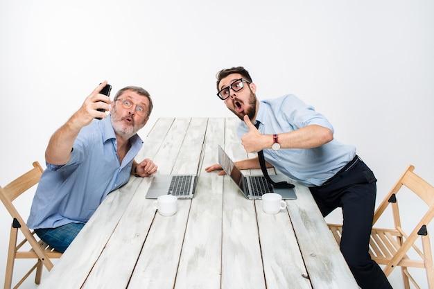 Dos colegas tomando la foto para sí mismos sentados en la oficina, sorprendieron a amigos con gafas tomando selfie con cámara de teléfono sobre fondo blanco.