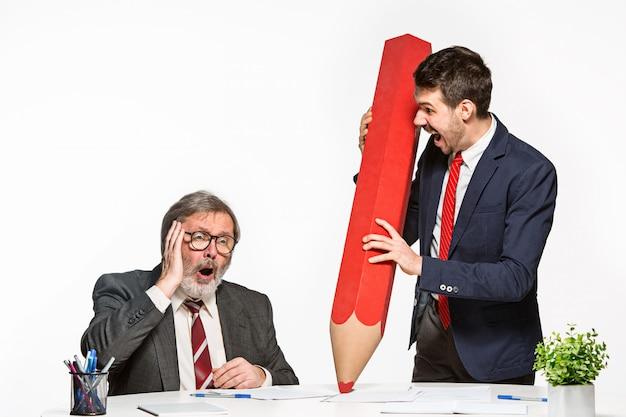 Los dos colegas trabajan juntos en la oficina con un enorme lápiz gigante.