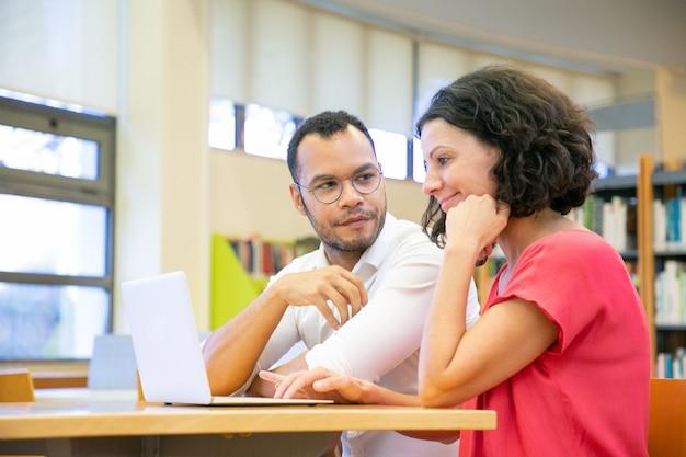Dos colegas trabajando en la presentación en la biblioteca.
