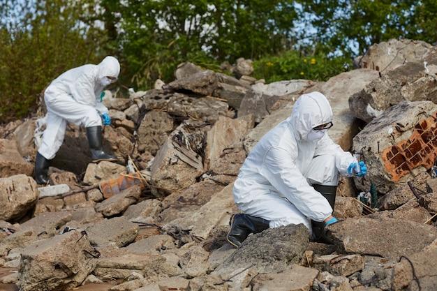 Dos colegas en trajes de protección sosteniendo frascos y tomando muestras al aire libre en una zona rural