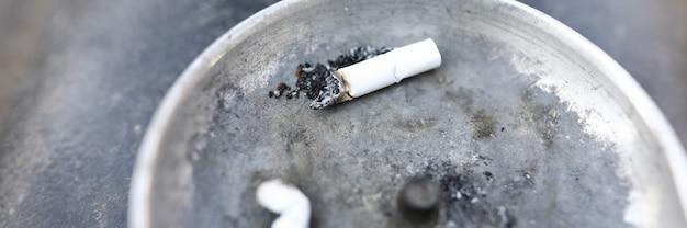 Dos colillas de cigarrillo blancas en el cenicero