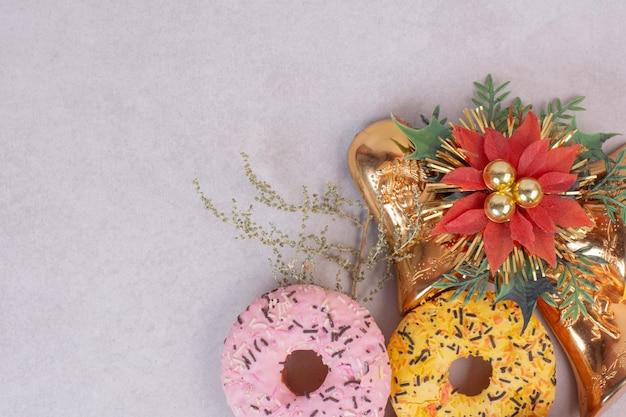 Dos coloridos donuts dulces sobre superficie blanca