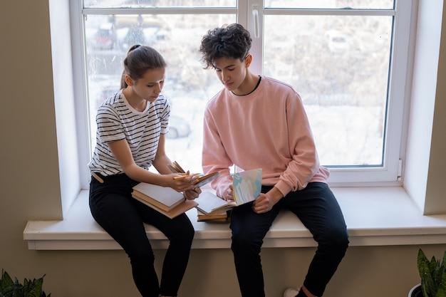 Dos compañeros adolescentes sentados junto a la ventana en el pasillo de la universidad en el descanso y discutiendo el pasaje del libro sostenido por la niña