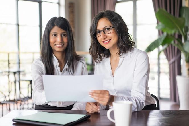 Dos compañeros de trabajo femeninos sonrientes que discuten el documento en café.