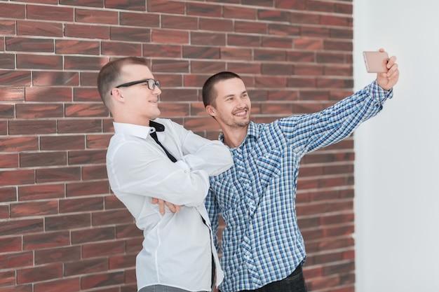 Dos compañeros de trabajo alegres tomando selfies de pie en la oficina .personas y tecnología.