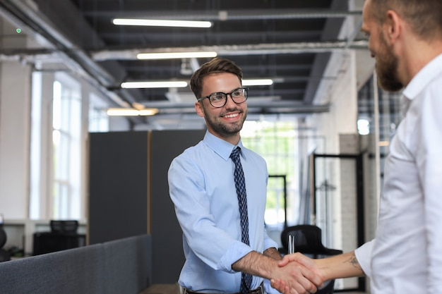 Dos compañeros de trabajo dándose la mano durante la reunión.