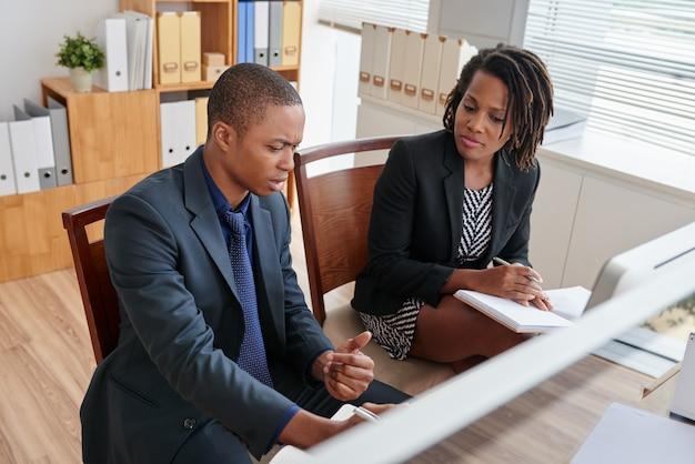 Dos compañeros de trabajo discutiendo ideas de negocios en una reunión