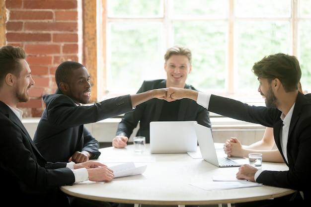 Dos compañeros de trabajo multiétnicos positivos se dan mutuamente el puño.