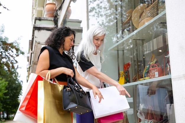 Dos compradores mujeres apuntando y mirando los accesorios en el escaparate, sosteniendo bolsas de la compra, de pie en la tienda exterior. vista lateral. concepto de escaparate