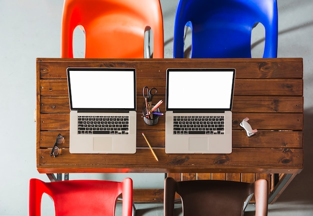 Dos computadoras portátiles abiertas con portalápices en mesa de madera con sillas de colores vacías