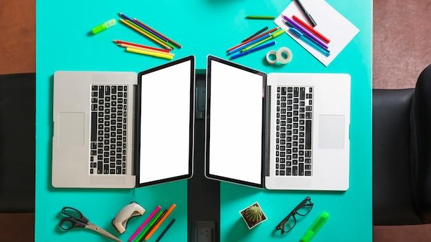 Dos computadoras portátiles con pantalla en blanco en el escritorio de la oficina con papelería y una silla cerca.
