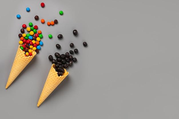 Dos conos de helado con diferentes dulces sobre un fondo gris