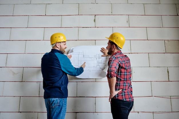 Dos constructores exitosos en cascos protectores discutiendo el plano mientras están de pie junto a la pared del edificio inacabado en la reunión de puesta en marcha