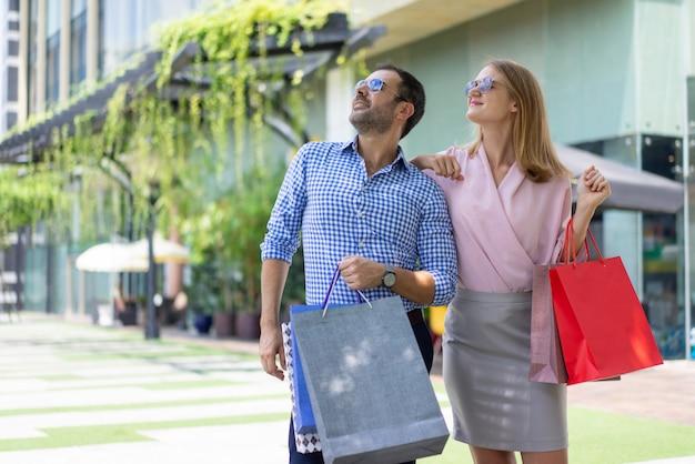 Dos consumidores felices atraídos por la publicidad en la pantalla de cartelera digital al aire libre.