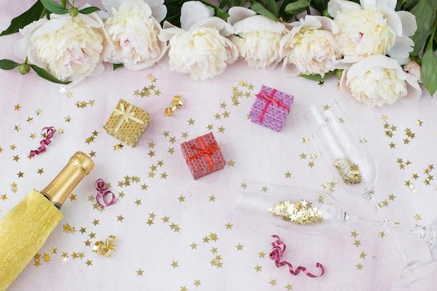 Dos copas, una botella de champagne, un ramo de peonías blancas, regalos y decoración festiva.