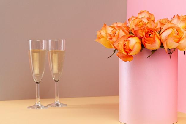 Dos copas con champagne y ramo de rosas.
