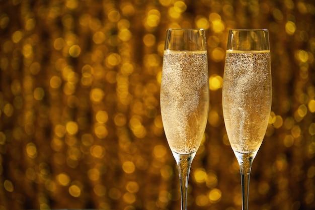 Dos copas de champagne sobre fondo dorado bokeh