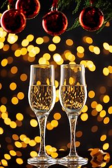 Dos copas de champán y adornos navideños sobre fondo de luces bokeh brillante