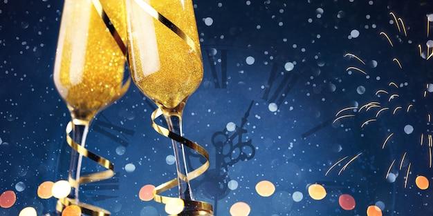 Dos copas de champán y cintas de oro con reloj de navidad sobre fondo azul.