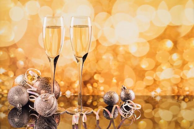 Dos copas de champán y decoración de navidad o año nuevo con luz dorada bokeh de fondo. cena romántica. concepto de vacaciones de invierno.