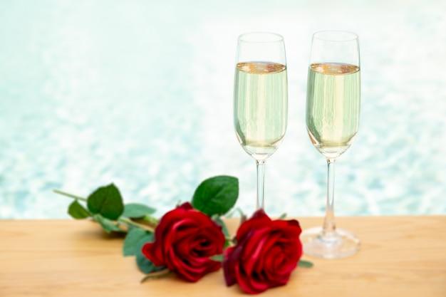 Dos copas de champán con flor rosa junto a la piscina.