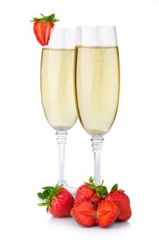 Dos copas de champán y fresas frescas aisladas en blanco