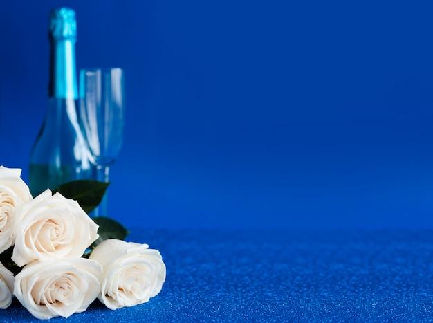 Dos copas de champán frío y un ramo de rosas blancas sobre fondo azul clásico.