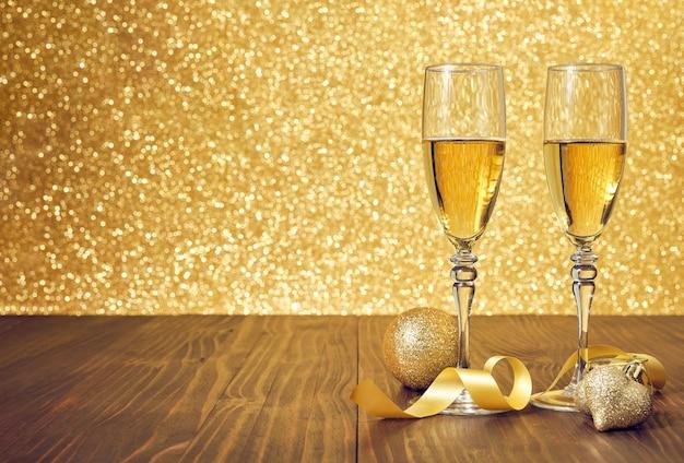 Dos copas de champán en una mesa de madera marrón con adornos navideños y fondo dorado desenfocado