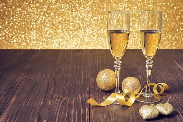 Dos copas de champán en una mesa de madera marrón con bolas de navidad doradas y fondo dorado brillante desenfocado